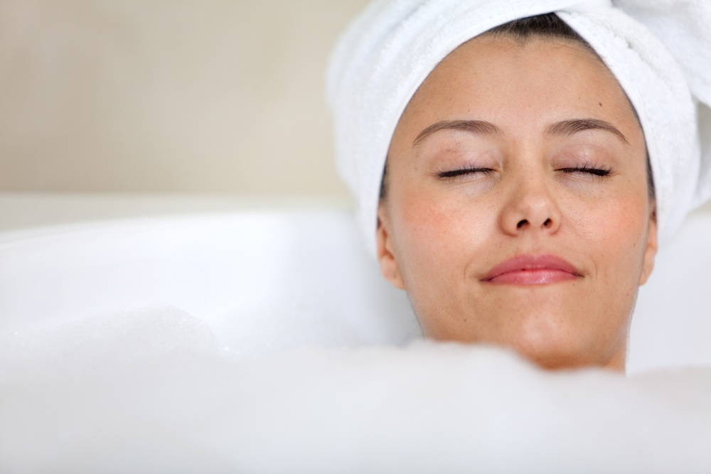 relaxed woman taking a bath with a towel on her head - Beauty concepts